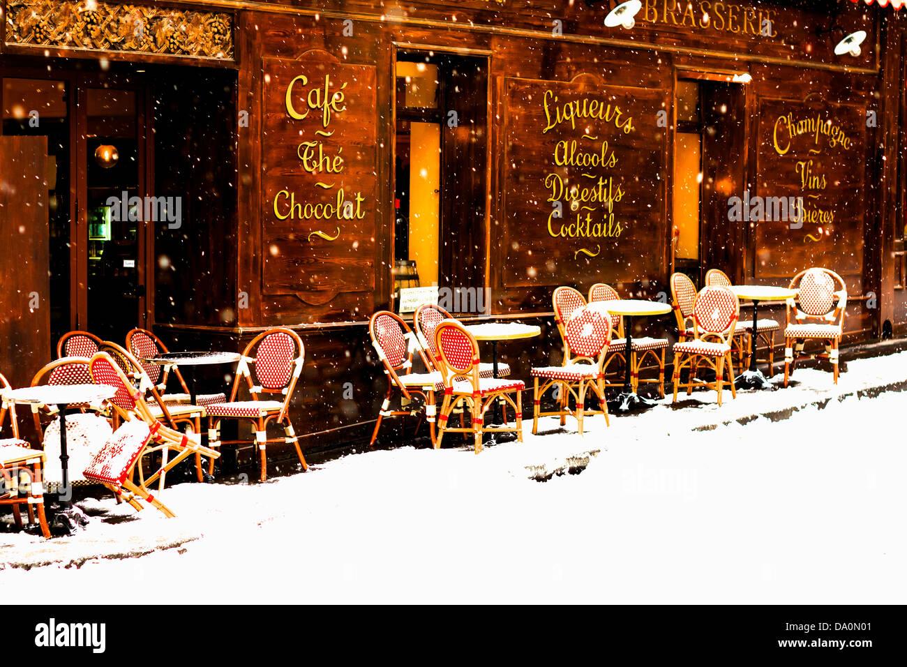 Maison en bois café parisien avec ses tables et chaises sur le trottoir en hiver avec la chute de neige Photo Stock