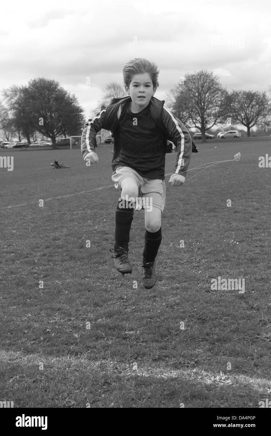 Kit de football de garçon sautant sur terrain de football Banque D'Images