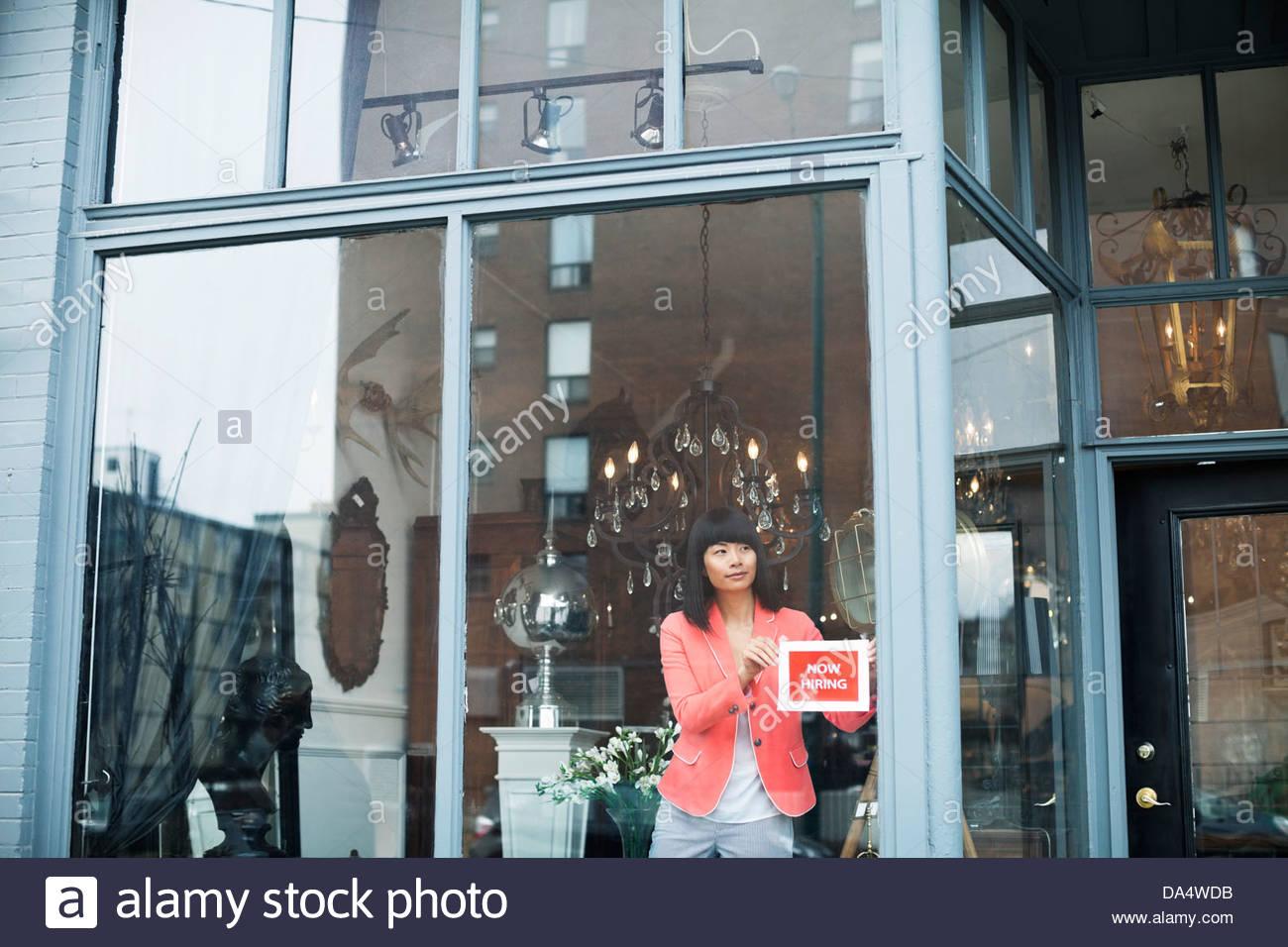 Femme propriétaire d'entreprise affichage de l'aide a voulu ouvrir une fenêtre de magasin de meubles Photo Stock