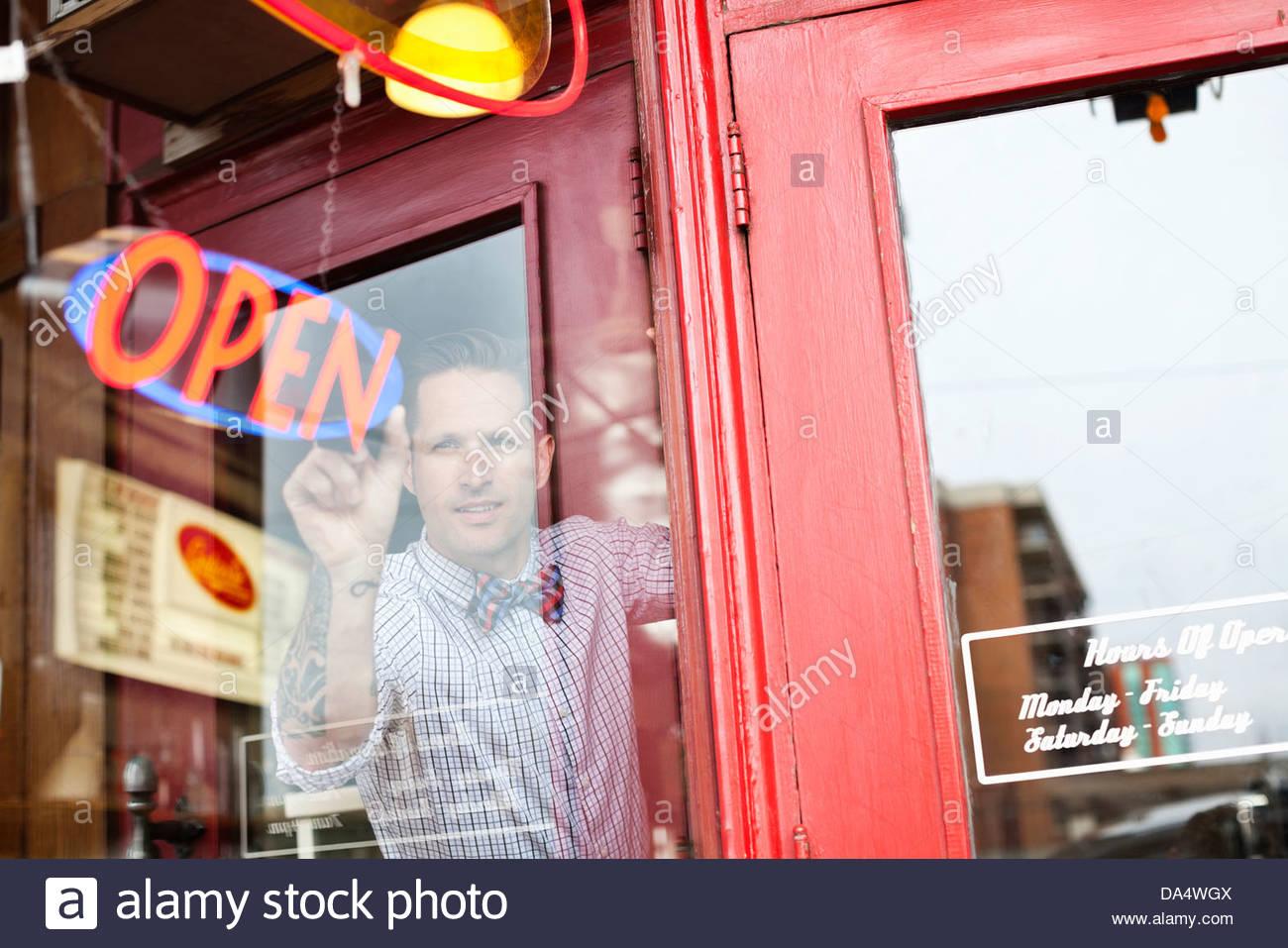 Réglage de l'homme propriétaire de l'entreprise open sign in diner window Photo Stock