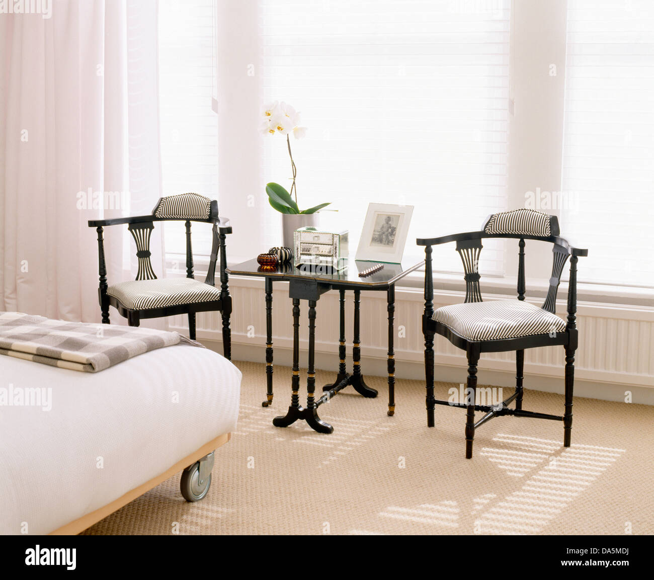 Mobilier de style édouardien chaises et petite table en face de la fenêtre dans la maison moderne chambre avec lit double sur roulettes