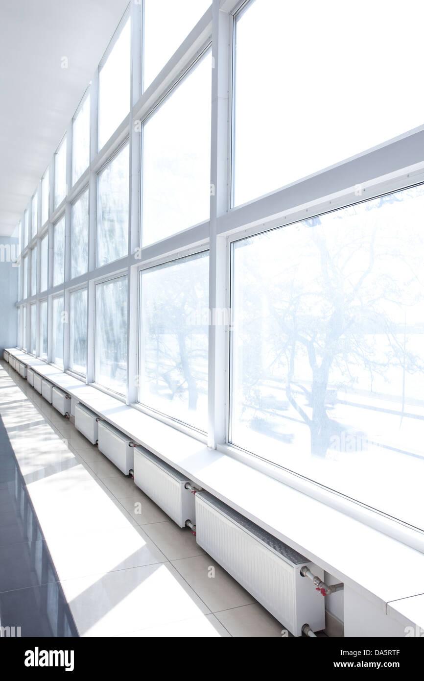 Salle vide avec de grandes fenêtres blanches et les radiateurs Banque D'Images