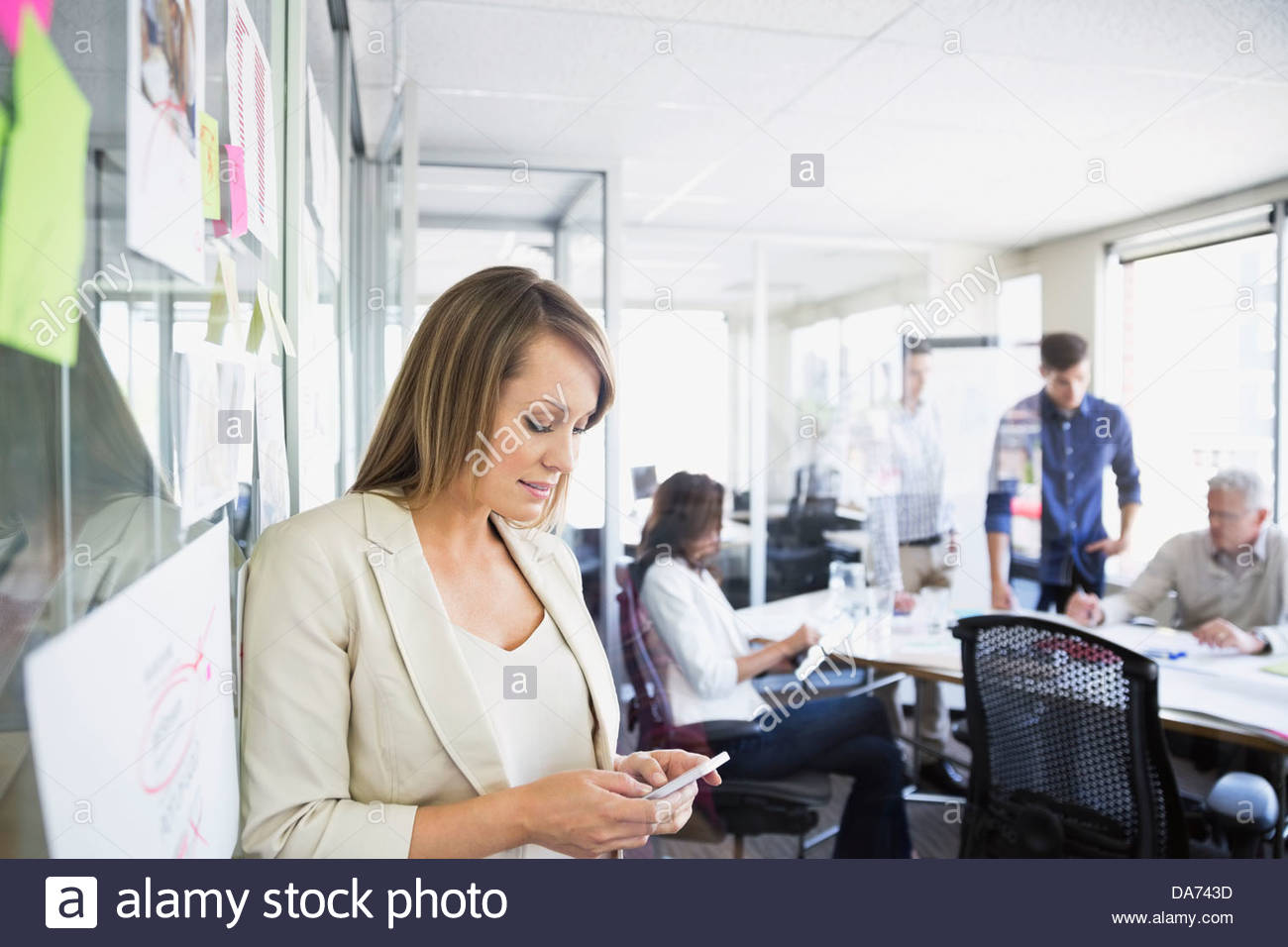 Businesswoman text messaging on mobile phone in office Banque D'Images