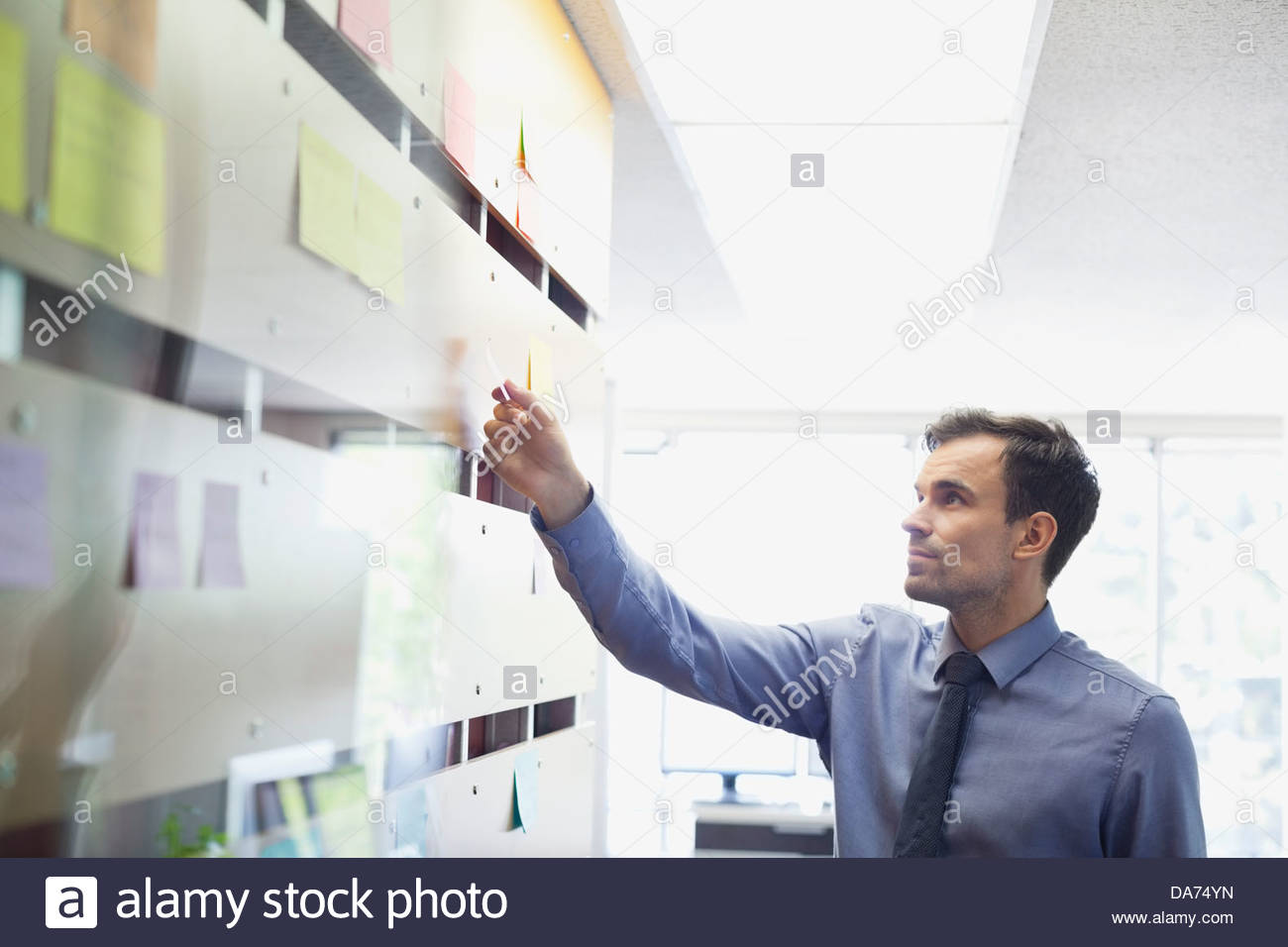 Businessman putting sticky note on wall Photo Stock