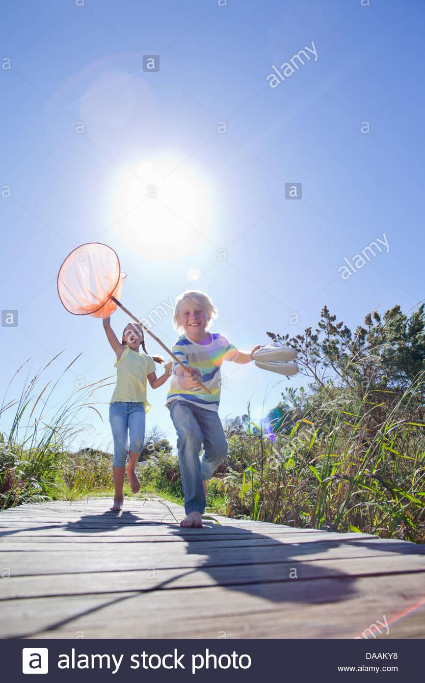 Garçon enthousiaste et fille courir pieds nus avec des filets de pêche Photo Stock