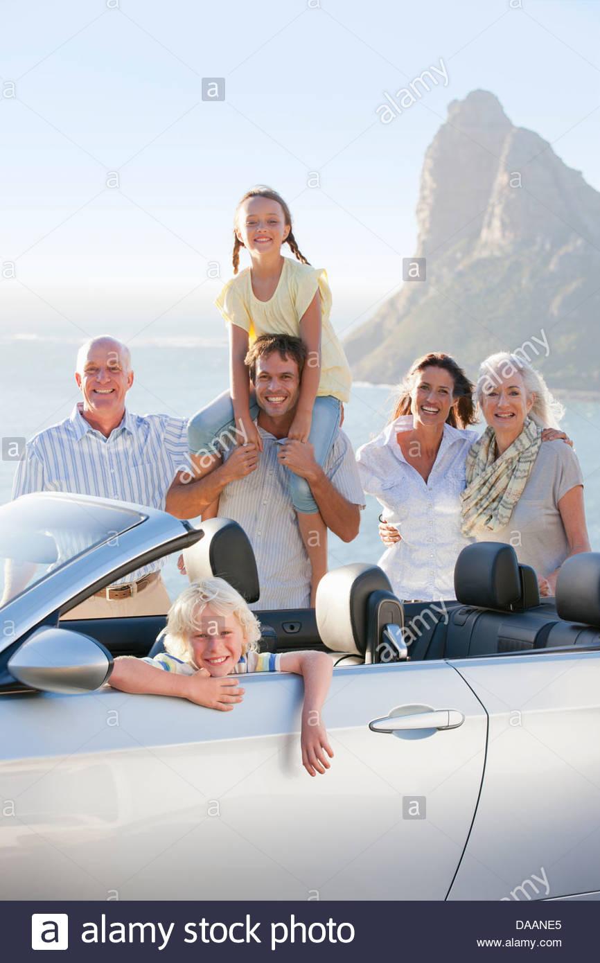 Portrait of smiling boy in convertible avec multi-generation family et de l'océan en arrière-plan Photo Stock