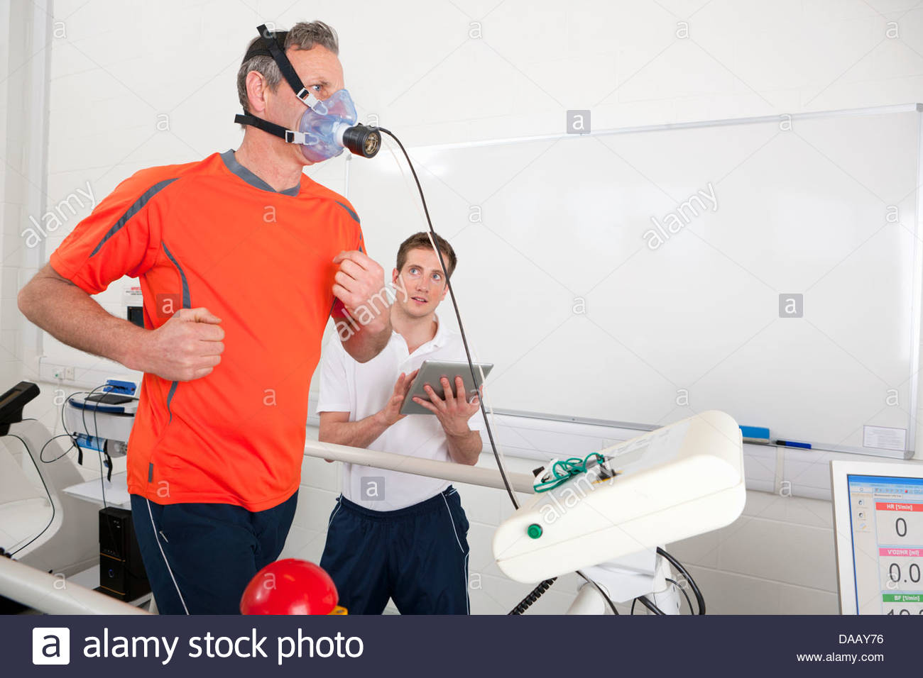 Sports scientist with digital tablet monitoring runner avec masque sur tapis roulant en laboratoire Photo Stock