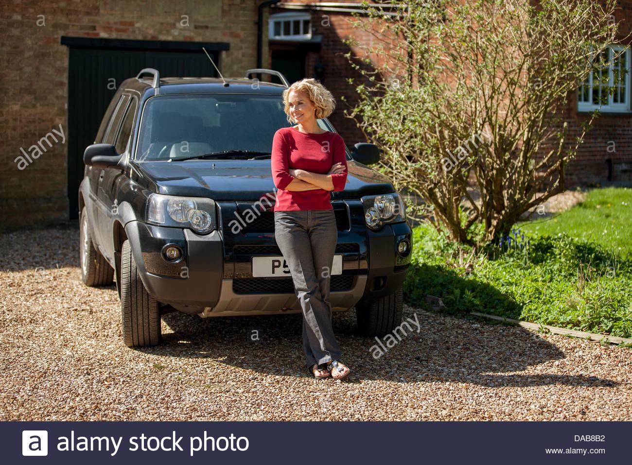 Une femme mature, debout devant une voiture à l'allée d'une maison Photo Stock