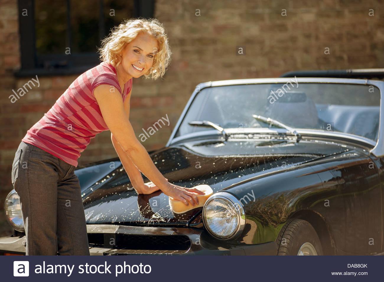Une femme mature lave une voiture de sport classique Photo Stock