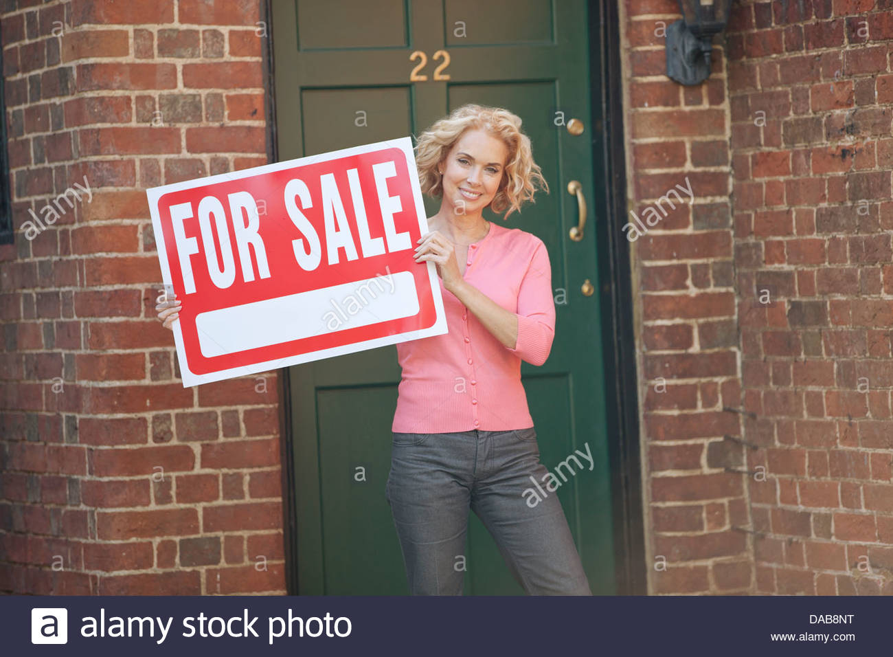 A young woman holding a property for sale sign Photo Stock