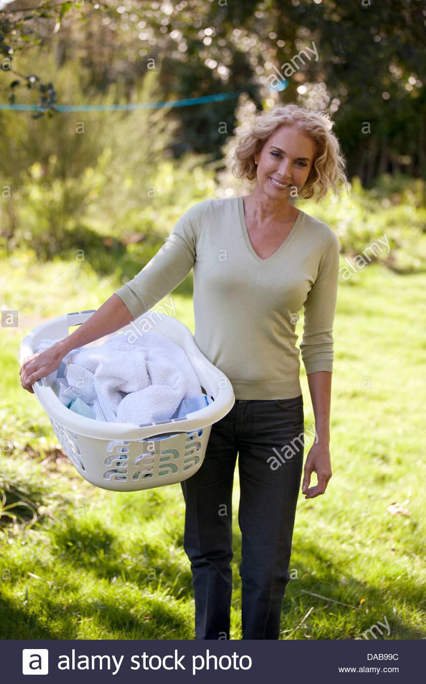 A mature woman holding un panier à linge à l'extérieur Photo Stock