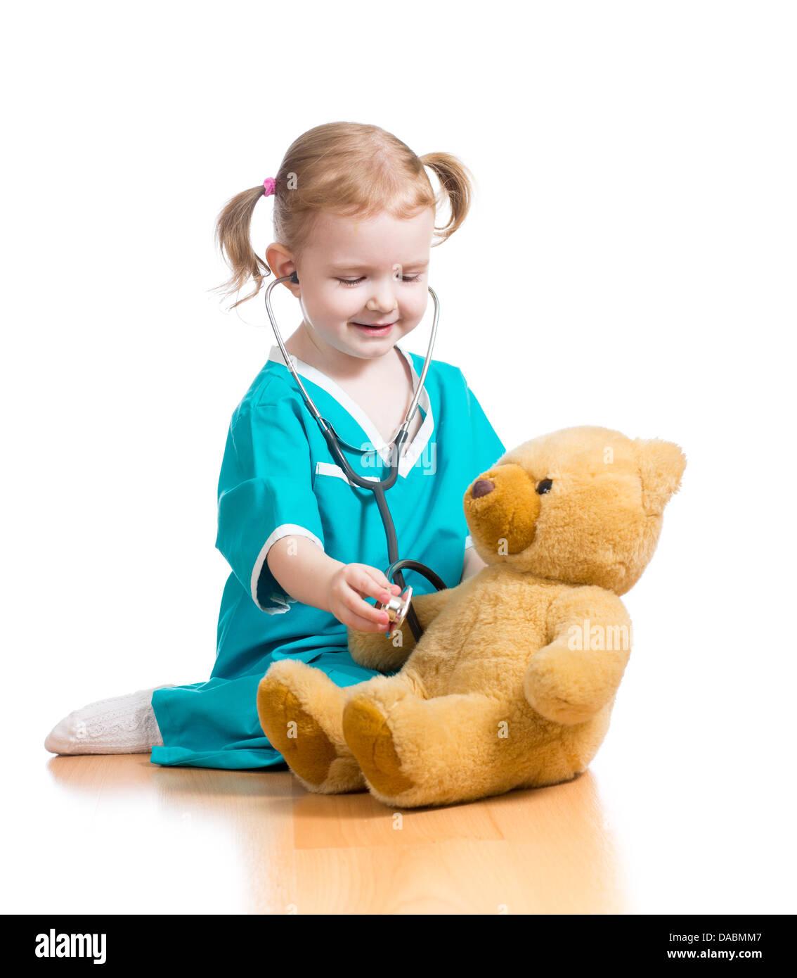 Vêtements enfant fille avec des médecin jouant avec peluche Photo Stock