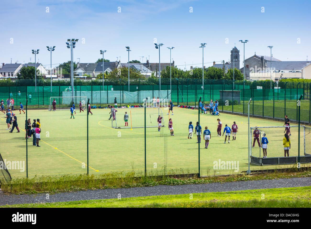 Les écoliers jouent au football sur un terrain par tous les temps - Dublin, Irlande Banque D'Images