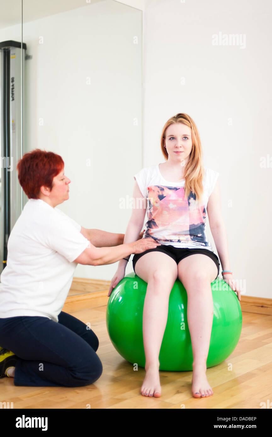 Young woman sitting on fitness ball, étant guidé par mature woman Photo Stock