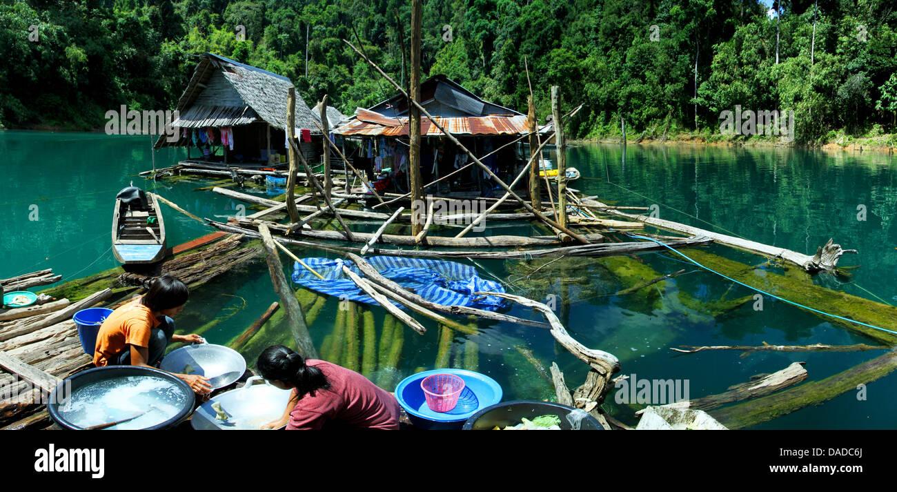 Cabanes sur Lan Chiao réservoir, les femmes laver la vaisselle, Thaïlande, parc national de Khao Sok Banque D'Images