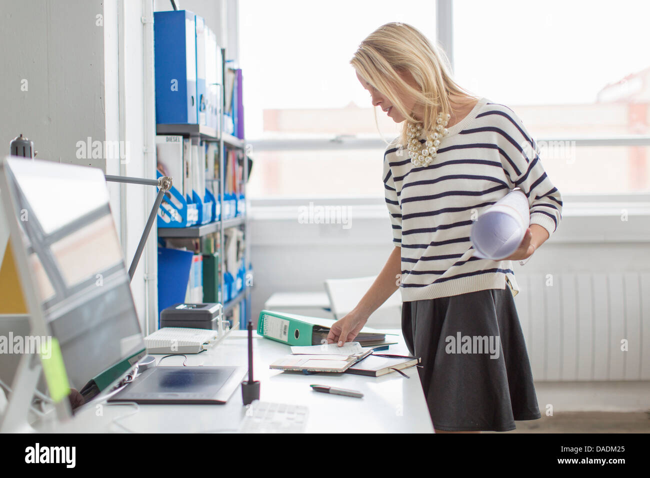 Young office worker holding plans au bureau en bureau de création Photo Stock