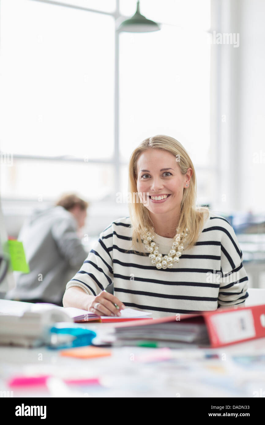 Young woman sitting at desk and smiling in creative office, portrait Photo Stock