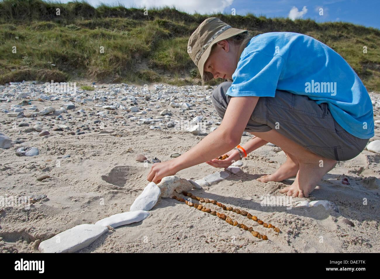 La création d'une fille de sculpture des pierres sur la plage de sable, Allemagne Photo Stock