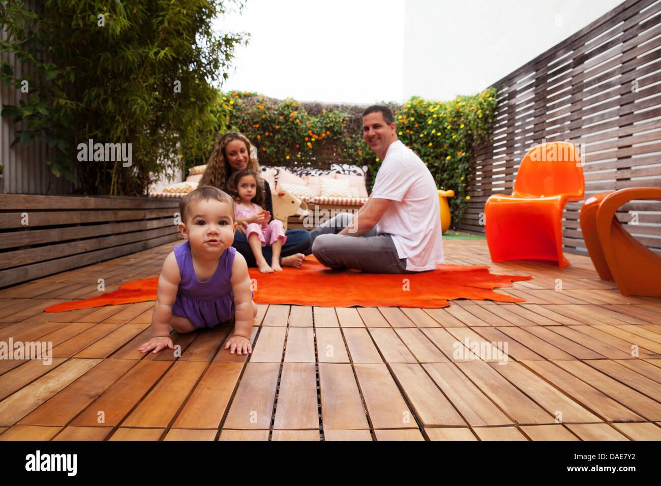 Family sitting on patio avec bébé fille ramper en premier plan Photo Stock
