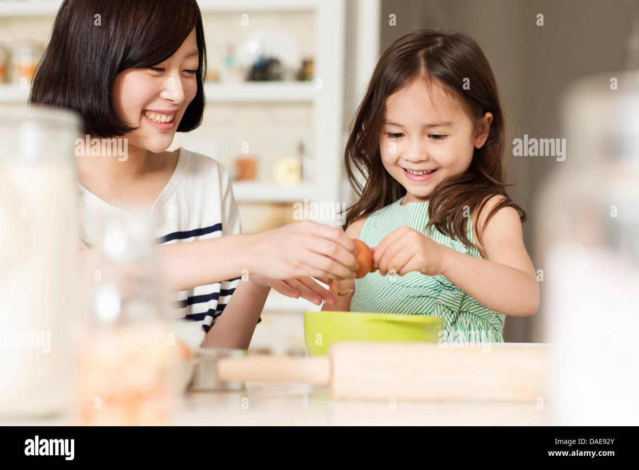Mère et fille, la fissuration oeuf dans bol Photo Stock
