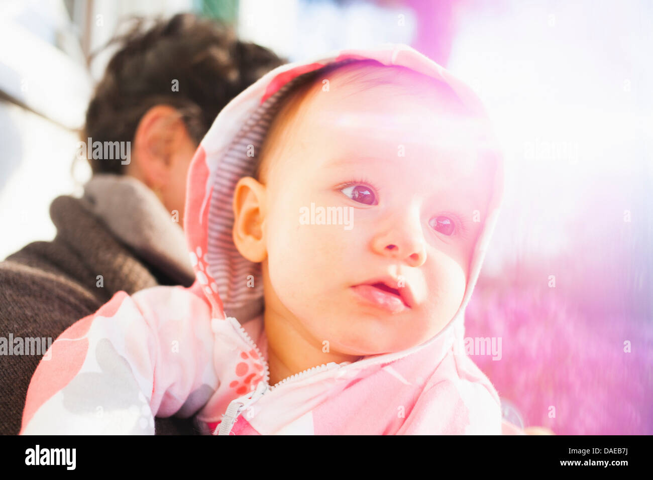 Close up portrait of baby girl wearing hood Photo Stock