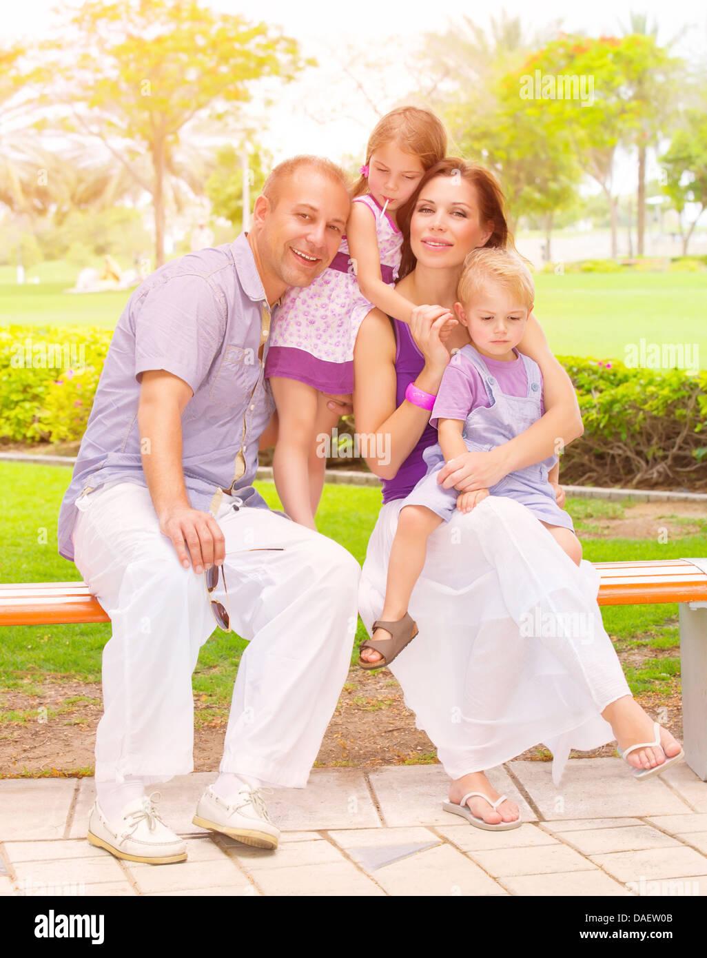 La famille mignon assis sur un banc dans le parc, vie active, petit frère et sœur avec un parent à l'extérieur, Photo Stock