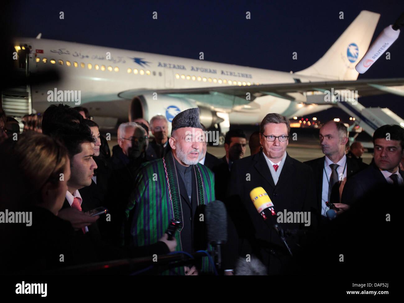 Le président afghan Hamid Karzaï (C) donne des interviews après avoir été accueilli par le ministre des Affaires étrangères allemand Guido Westerwelle (3-R) après son arrivée à l'aéroport de Cologne-Bonn à Cologne, Allemagne, 02 décembre 2011. Hamid Karzai a la présidence de la Conférence internationale sur l'Afghanistan à Bonn le 05 décembre 2011. Photo: OLIVER BERG Banque D'Images