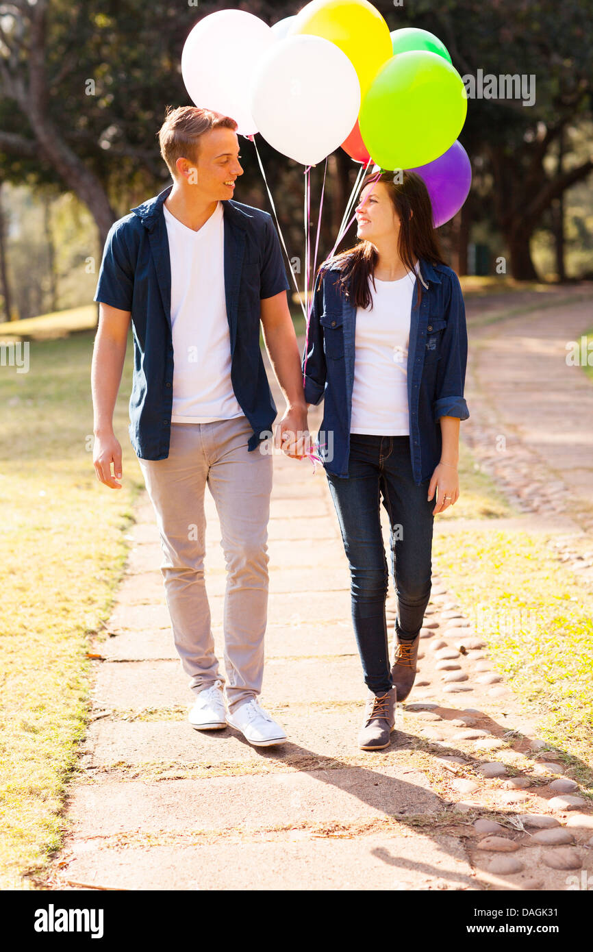 Adorable teenage couple en train de marcher dans le parc holding hands Photo Stock
