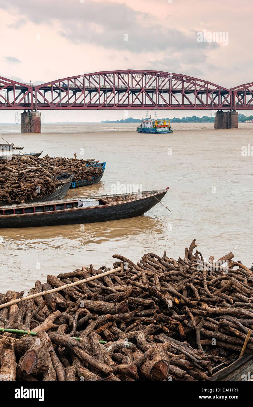 Bateaux chargés de bois de chauffage pour alimenter la crémation ghats le long du Gange à Varanasi Photo Stock