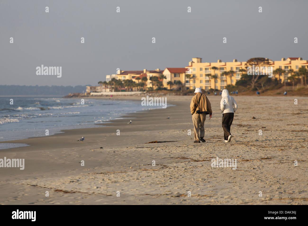 Un couple de retraités âgés marchant sur une plage vide au lever du soleil Photo Stock