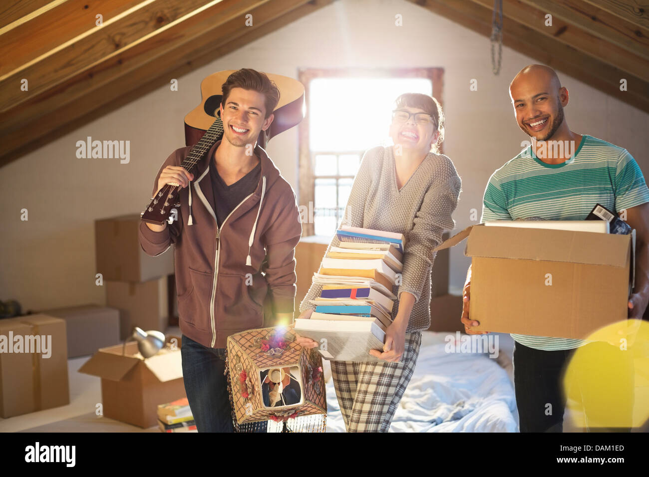 Friends unpacking boxes in attic Photo Stock