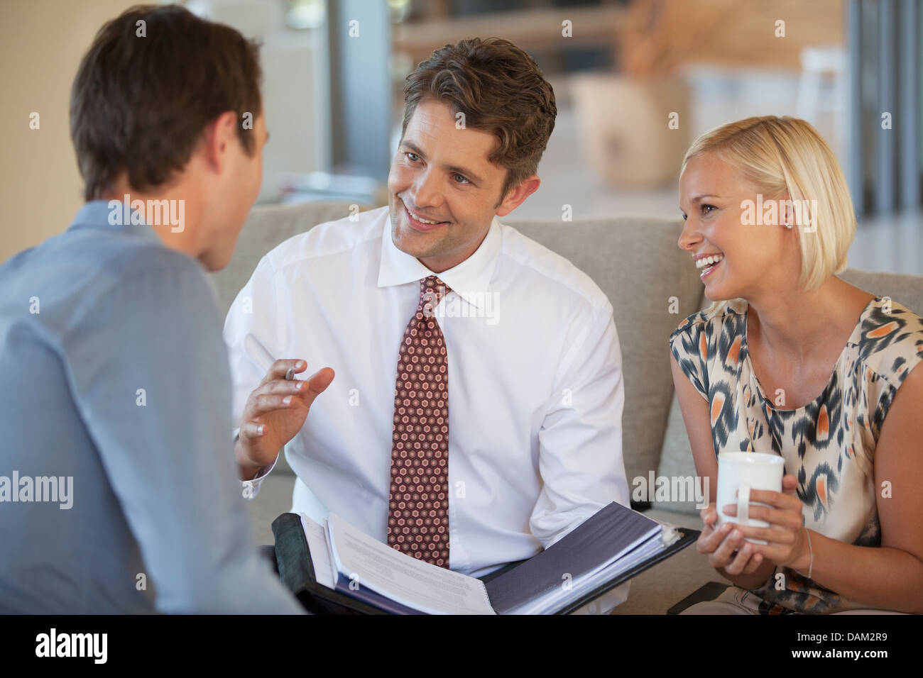 Financial Advisor talking to couple on sofa Banque D'Images