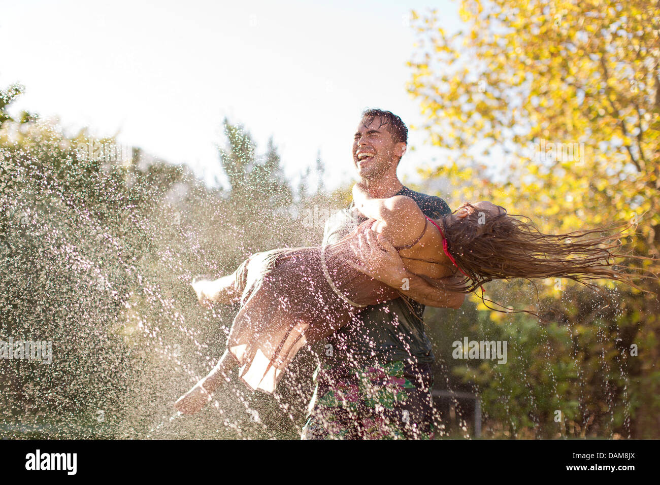 Couple playing in backyard sprinkleur Photo Stock