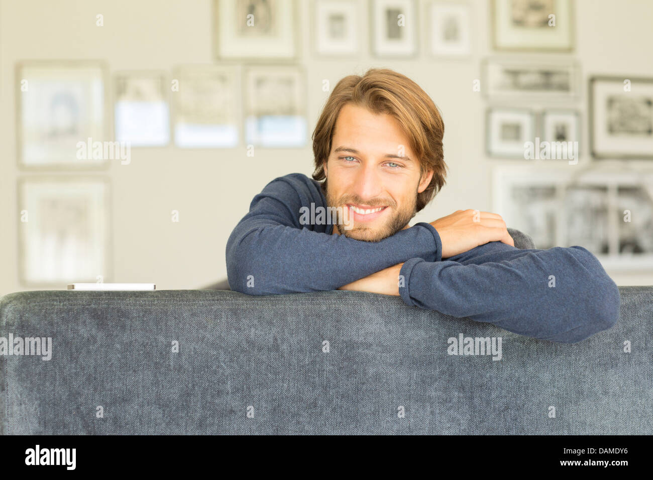 Smiling man sitting on sofa Banque D'Images