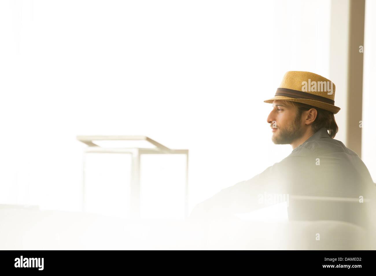 L'homme à chapeau de paille looking out window Photo Stock