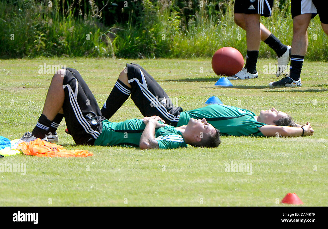 Les joueurs de Wolfsburg Diego Benaglio (L) et Marwin Hitz étendu sur le sol dans un circuit d'entraînement Photo Stock