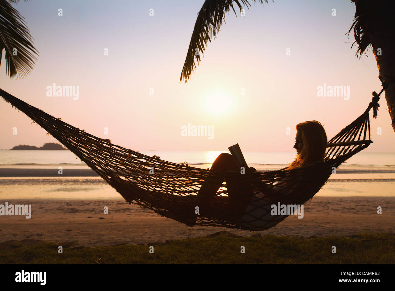 Silhouette of woman relaxing in hammock sur la plage Photo Stock