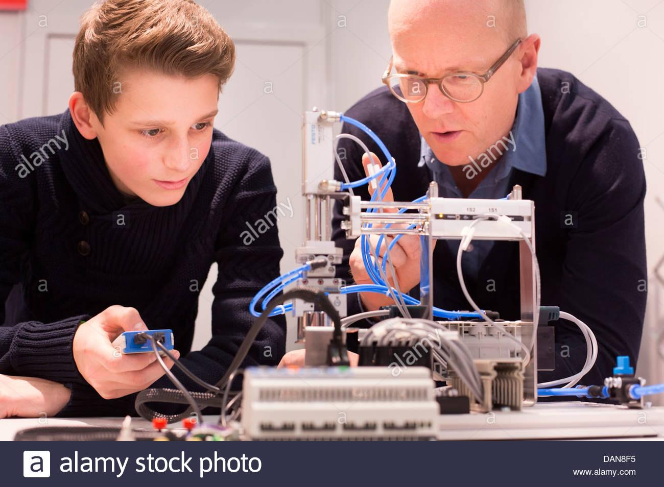Étudiant avec un enseignant à l'aide du modèle de régulation de débit pneumatique Photo Stock