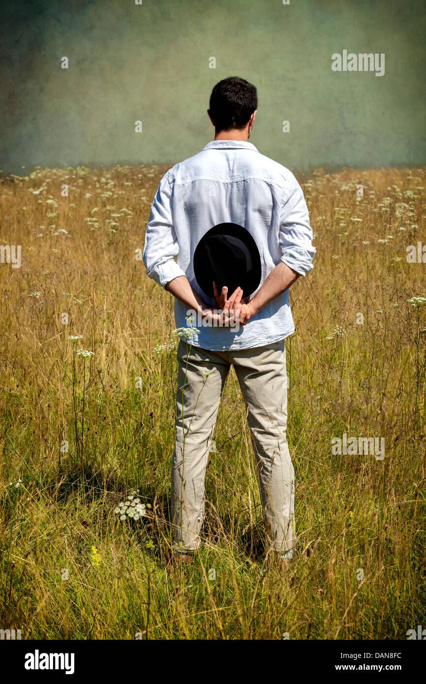 Un homme avec un chapeau noir debout sur un champ Photo Stock