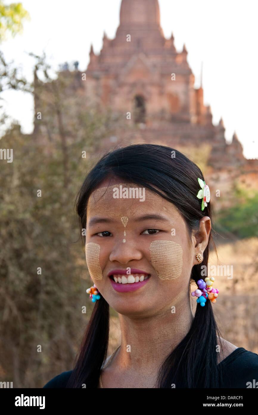 Jeune femme avec de l'écorce de thanaka maquillage avec Bagan temple bouddhiste en arrière-plan. Photo Stock