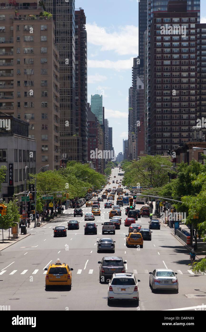 Dans la rue longue avec le trafic dans la ville de New York Photo Stock