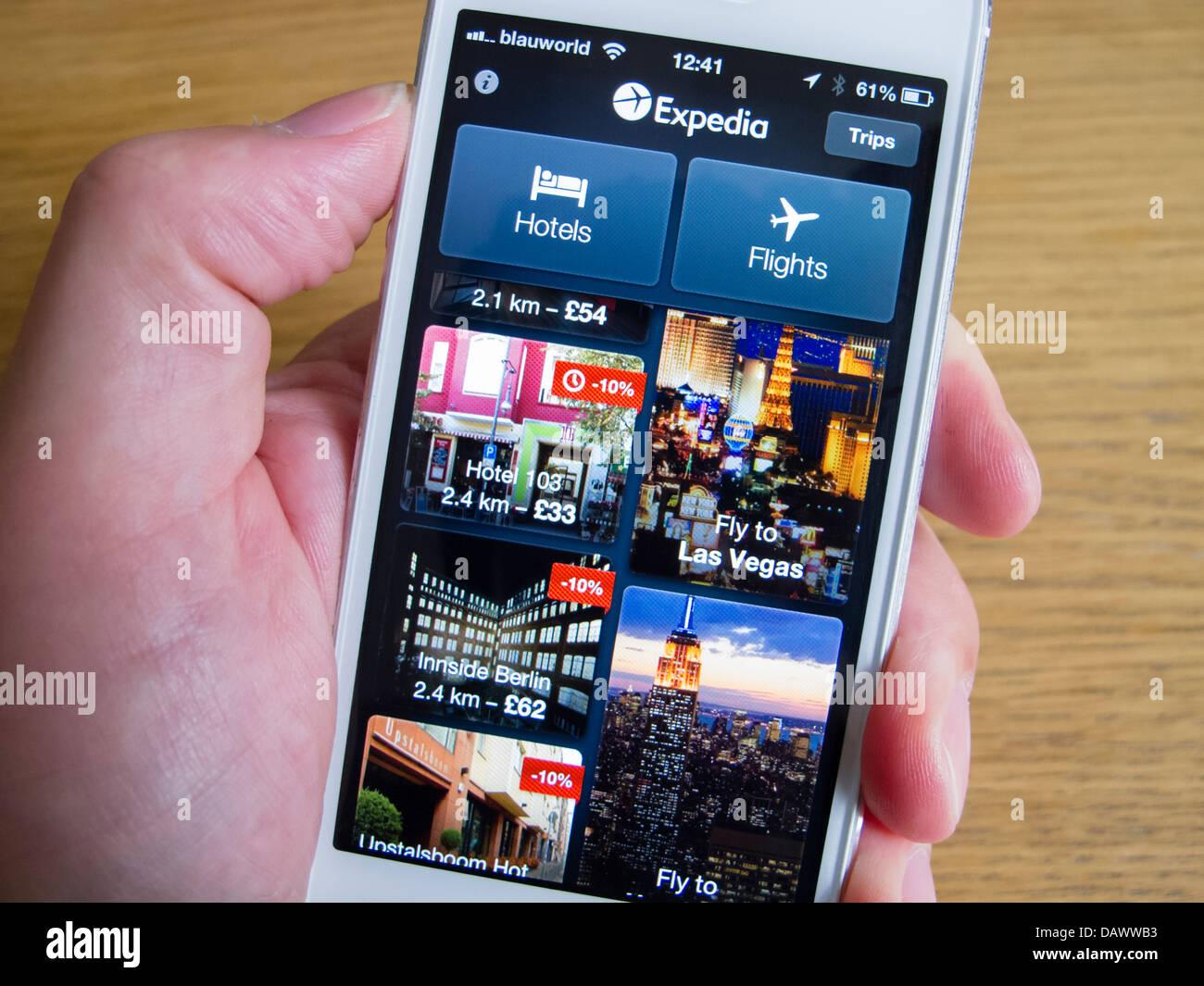 En utilisant app Expedia pour réserver des voyages sur smartphone iPhone 5 blanc Photo Stock