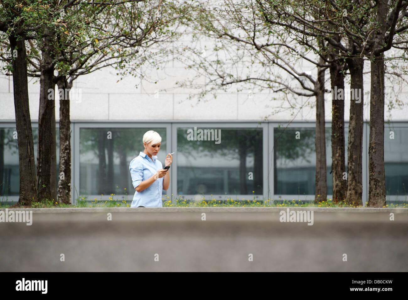 Young businesswoman cigarette au cours de sortir du bâtiment de bureaux. Plan d'ensemble, copy space Photo Stock