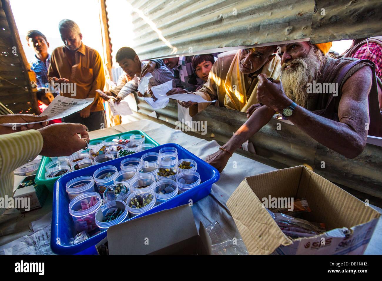 Les gens recueillir des médicaments dans un dispensaire de champ à la Kumbh Mela à Allahabad, Inde Photo Stock