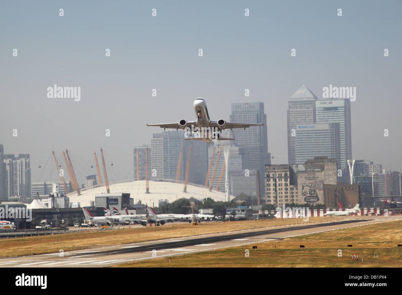 Un jet de passagers décolle de l'aéroport de London City avec Canary Wharf et le dôme du millénaire Photo Stock
