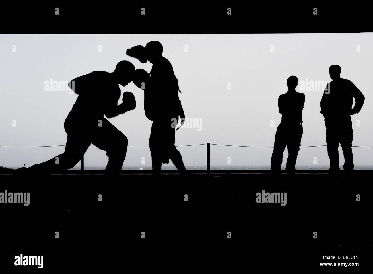 Les marins de l'US Navy dans le hangar de boxe pratique Bay à bord du porte-avions USS Nimitz silhouetté Photo Stock