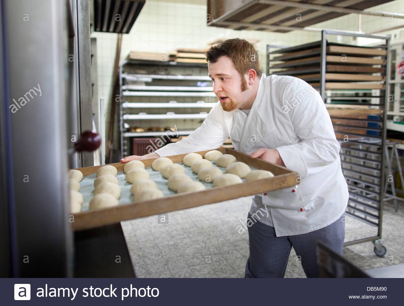 Petits pains cuisson Chef dans une boulangerie Photo Stock