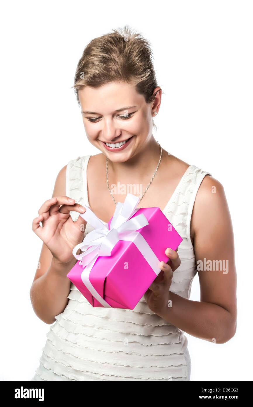 Très jolie femme tenant un cadeau et qu'il déroule, isolé sur fond blanc Photo Stock
