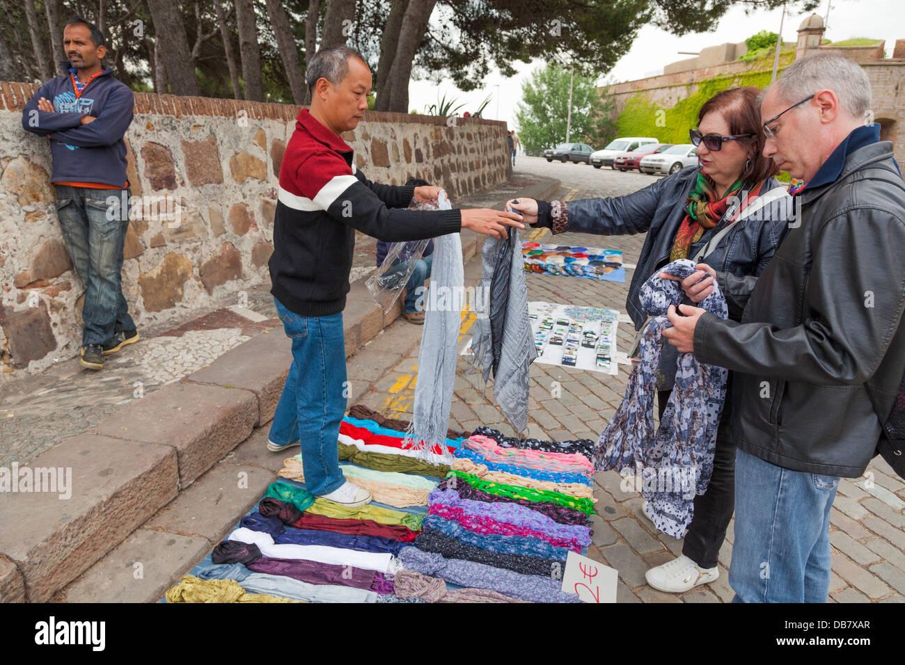 Les vendeurs de rue vendant des écharpes de chaussée à château de Montjuic, Barcelone. Photo Stock