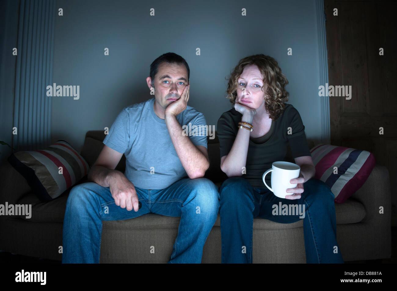 Couple d'âge moyen dans une relation à regarder la télévision s'ennuyer Banque D'Images